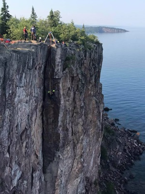 rock climbers at the top of a steep cliff